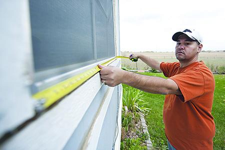Home weatherization worker measuring window